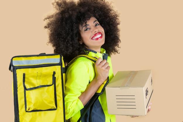 Ładna kobieta dostarczająca afro z pudełkiem w dłoni, szczęśliwa uśmiechnięta, beżowe tło