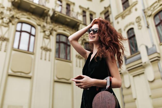 Ładna kobieta dotyka jej włosów i pozuje na zewnątrz w okularach przeciwsłonecznych