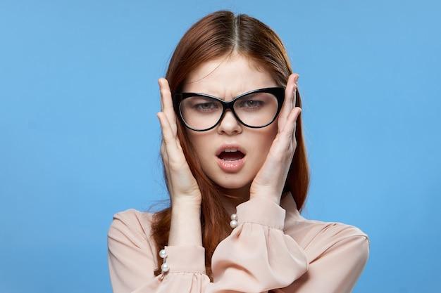 Ładna kobieta elegancki styl okulary moda emocje ręce w pobliżu twarzy niebieski.
