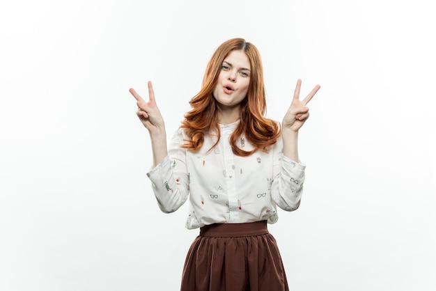Ładna kobieta gestykuluje rękami z rudymi włosami