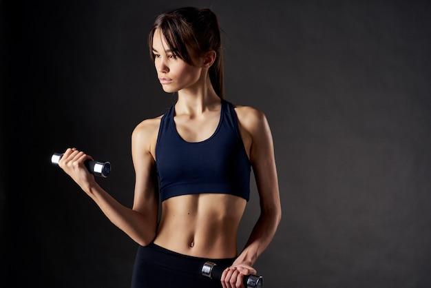 Ładna kobieta hantle ćwiczeń fitness w rękach silnego na białym tle. zdjęcie wysokiej jakości