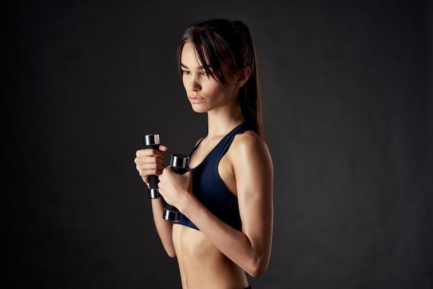 Ładna kobieta hantle do ćwiczeń fitness w rękach mocnego ciemnego tła