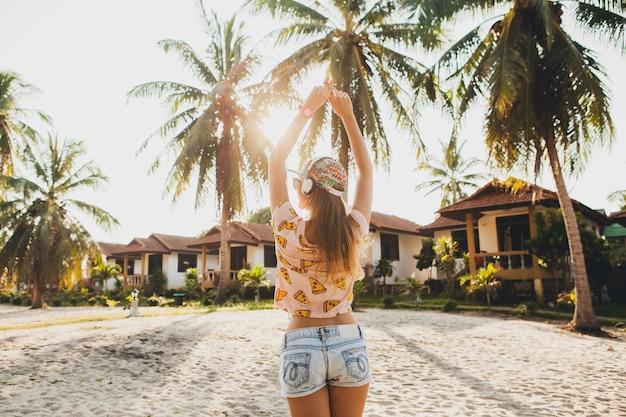 Ładna kobieta hipster chodzenie po plaży, taniec, słuchanie muzyki na słuchawkach w stylowym, kolorowym stroju na słonecznych letnich tropikalnych wakacjach noszenie akcesoriów czapka okulary przeciwsłoneczne, uśmiechanie się, zabawy
