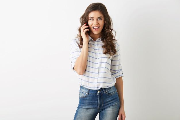 Ładna kobieta hipster styl studencki strój rozmawia na smartfonie, uśmiecha się, patrząc w kamerę, atrakcyjny model za pomocą telefonu komórkowego, swobodny strój, podekscytowany wyraz twarzy, na białym tle, komunikacja