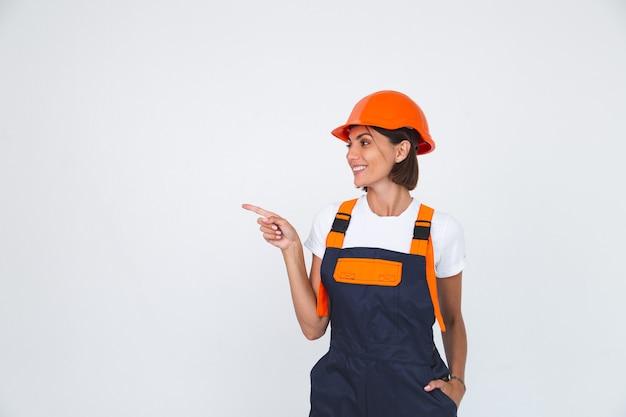 Ładna kobieta inżynier w budowie hełmu ochronnego na białym, pewnie uśmiechniętym palcu wskazującym w lewo