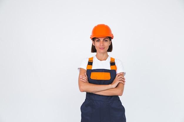 Ładna kobieta inżynier w budowie hełmu ochronnego na białym pewnym uśmiechu skrzyżowanymi ramionami