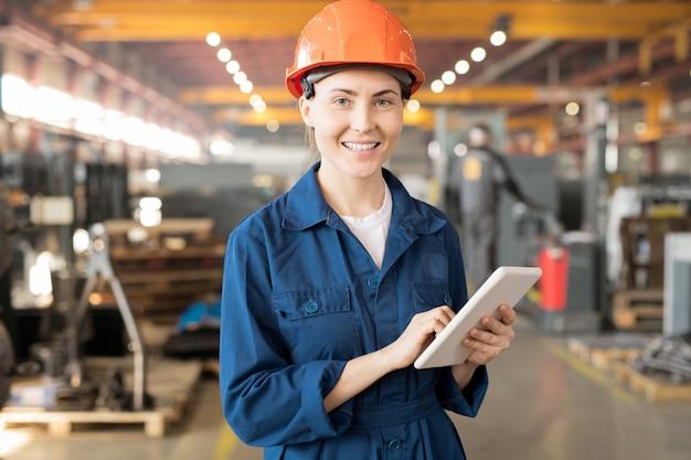 Ładna kobieta-inżynier z zębatym uśmiechem, trzymając tablet i surfując w sieci, szukając danych online