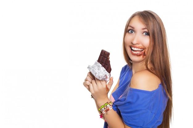 Ładna kobieta je czekoladę obiema rękami, niektóre w ustach. isolatet na białym tle.