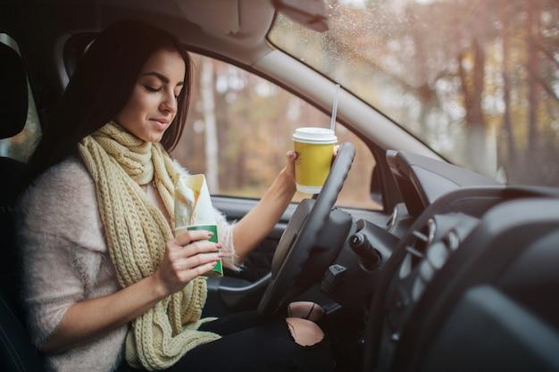 Ładna kobieta je jedzenie i jedzie w jej samochodzie