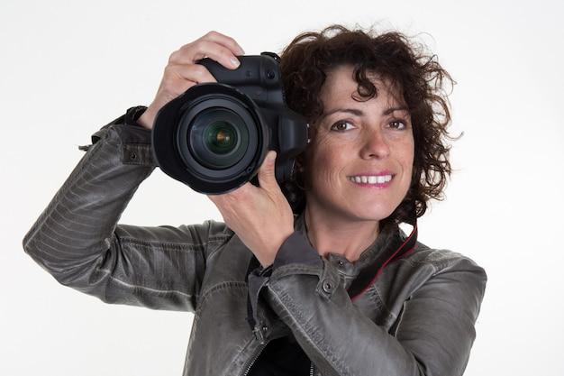 Ładna kobieta jest profesjonalnym fotografem z aparatem dslr