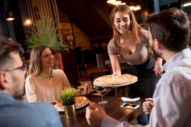 Ładna kobieta kelner obsługująca grupę przyjaciół z jedzeniem w restauracji