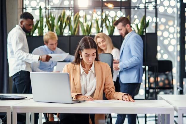 Ładna kobieta kierownik biura siedzi przy stole roboczym i używa dwóch laptopów w biurze na tle swoich biurowych kolegów