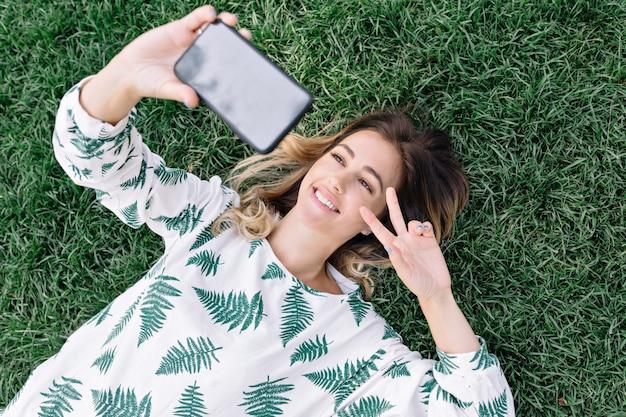 Ładna kobieta, kładąc na trawie w parku i robiąc selfie na swoim telefonie i pokazuje znak pokoju