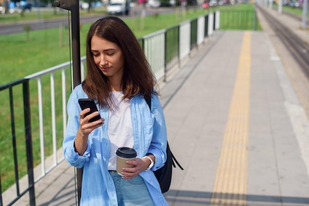 Ładna kobieta korzysta z inteligentnego telefonu i pije poranną kawę, czekając tramwajem lub autobusem na stacji publicznej.