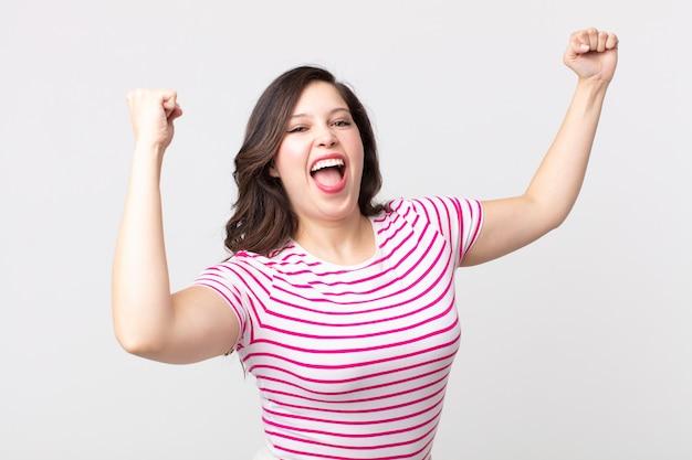 Ładna kobieta krzycząca triumfalnie, wyglądająca jak podekscytowana, szczęśliwa i zaskoczona zwycięzca, świętuje
