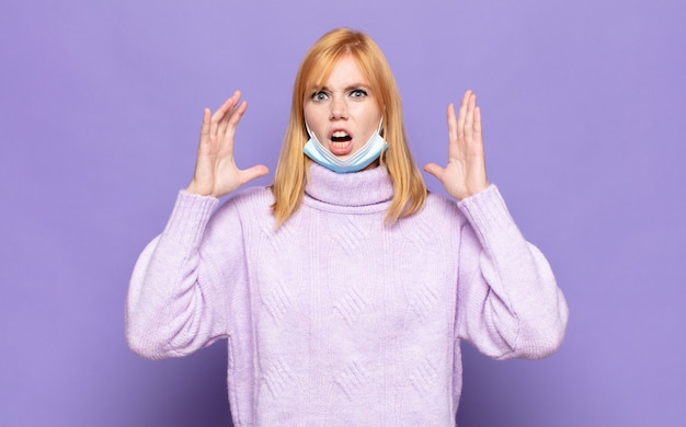 Ładna kobieta krzycząca z podniesionymi rękami, wściekła, sfrustrowana, zestresowana i zdenerwowana