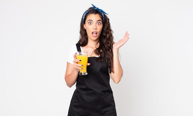 Ładna kobieta krzycząca z rękami w górze i trzymająca szklankę soku pomarańczowego
