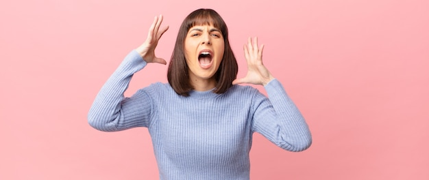 Ładna kobieta krzycząca z rękami w górze, wściekła, sfrustrowana, zestresowana i zdenerwowana