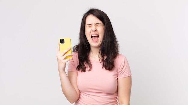 Ładna kobieta krzyczy agresywnie i wygląda na bardzo złą, używając smartfona