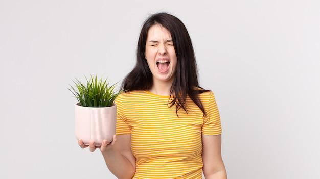 Ładna kobieta krzyczy agresywnie, wygląda na bardzo złą i trzyma ozdobną roślinę