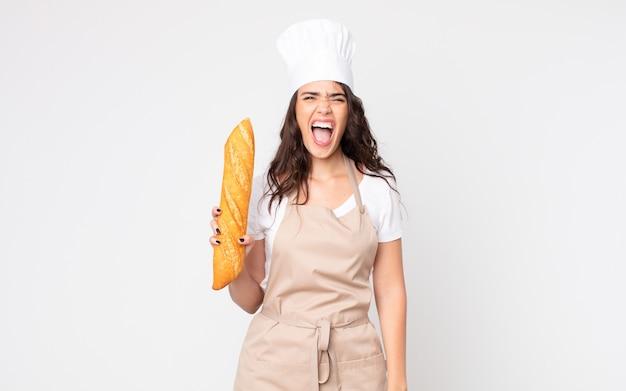 Ładna kobieta krzyczy agresywnie, wygląda na bardzo złą w fartuchu i trzyma bagietkę z chlebem