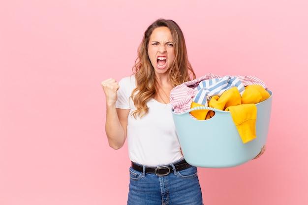 Ładna kobieta krzyczy agresywnie z gniewnym wyrazem twarzy i pranie.