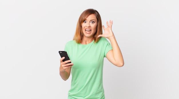 Ładna kobieta krzyczy z rękami w górze i używa smartfona