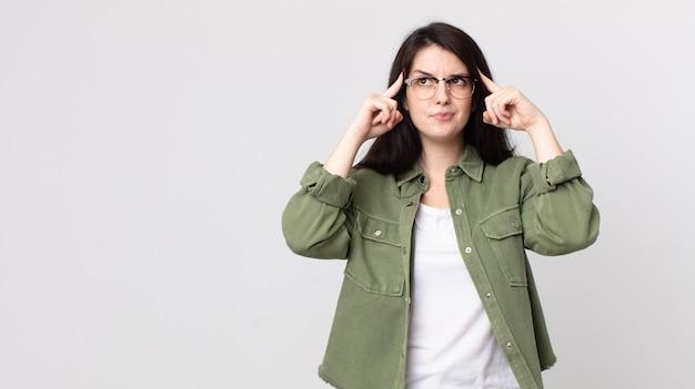 Ładna kobieta, która wygląda na skoncentrowaną i intensywnie myśli o pomyśle, wyobrażając sobie rozwiązanie wyzwania lub problemu