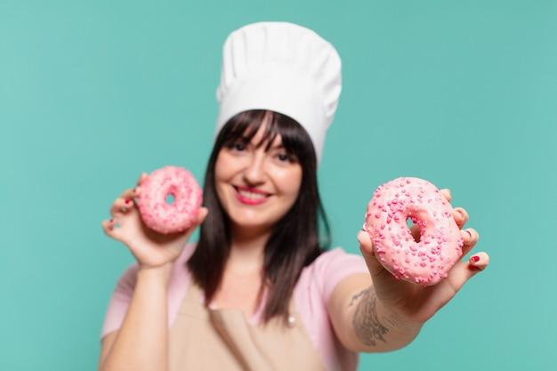Ładna kobieta kucharz szczęśliwa ekspresja i trzymająca pączki