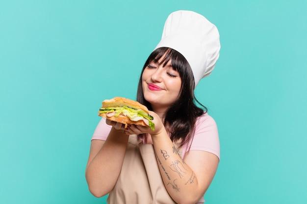 Ładna kobieta kucharz szczęśliwy wyraz twarzy i trzymająca kanapkę