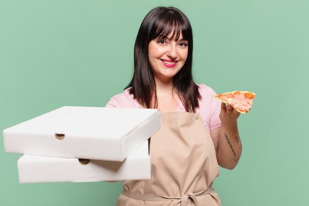 Ładna kobieta kucharz szczęśliwy wyraz twarzy i trzymająca pizzę