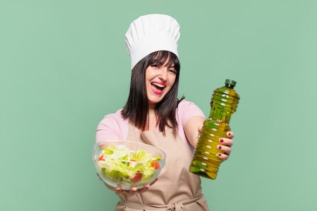 Ładna kobieta kucharz szczęśliwy wyraz twarzy i trzymająca sałatkę