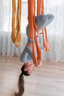 Ładna kobieta latać jogi wisi do góry nogami z zamkniętymi oczami