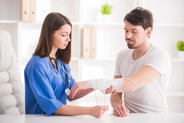 Ładna kobieta lekarz bandażuje kończynę górną młodego człowieka.