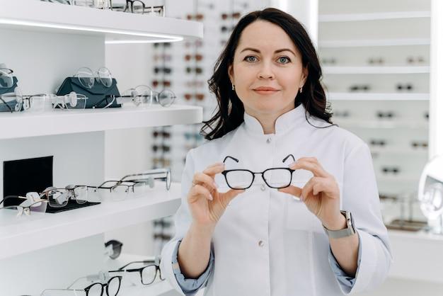 Ładna kobieta lekarz trzymając okulary w dłoniach