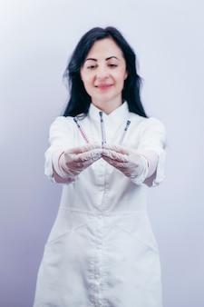 Ładna kobieta lekarz ubrana w biały szlafrok medyczny i trzymając strzykawkę w szarej przestrzeni