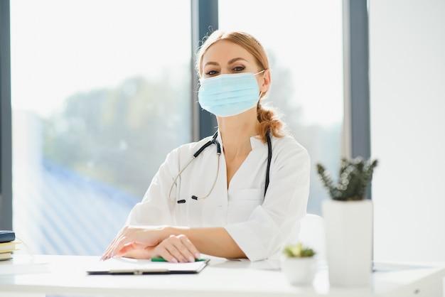 Ładna kobieta lekarz w masce ochronnej w szpitalu