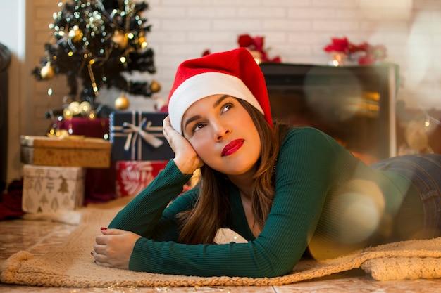 Ładna kobieta, leżąc na dywanie w salonie swojego domu z ozdób choinkowych i prezentów na drzewie.