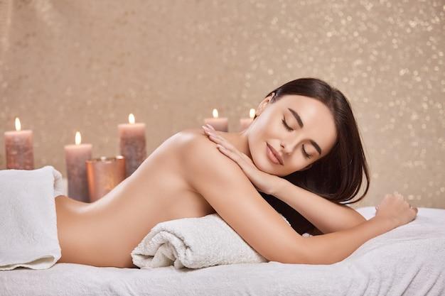 Ładna kobieta leży na stole do masażu z zamkniętymi oczami i nagimi plecami
