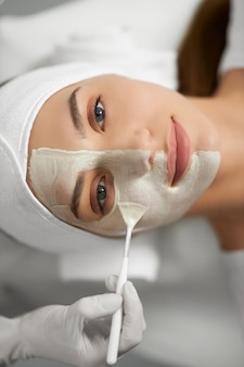 Ładna kobieta leży na zabiegu odmładzania skóry