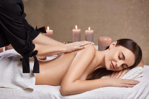 Ładna kobieta leży w spa z nagimi plecami i otrzymuje masaż i zabieg na skórę