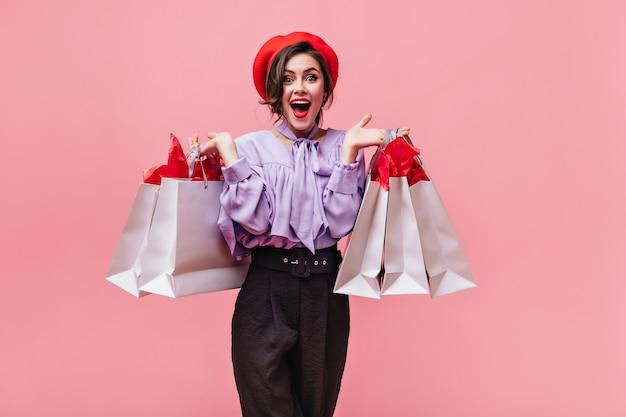 Ładna kobieta lubi udane zakupy i pozuje z torbami. portret zielonookiej dziewczyny z chrupiącymi ustami na różowym tle.