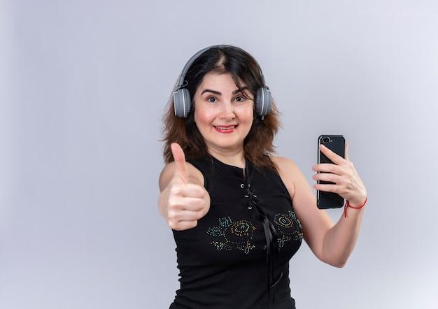 Ładna kobieta ma na sobie czarną bluzkę patrząc robi szczęśliwy kciuki do góry w słuchawkach trzymając telefon