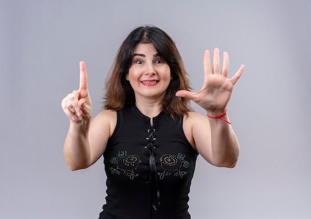 Ładna kobieta ma na sobie czarną bluzkę pokazując jeden i pięć z palcami