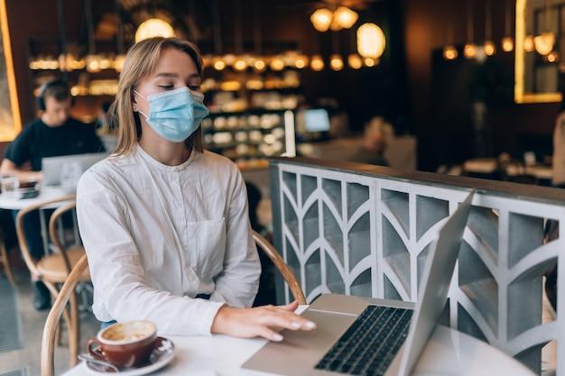 Ładna kobieta ma na sobie maskę medyczną za pomocą laptopa do pracy