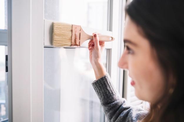 Ładna kobieta maluje okno