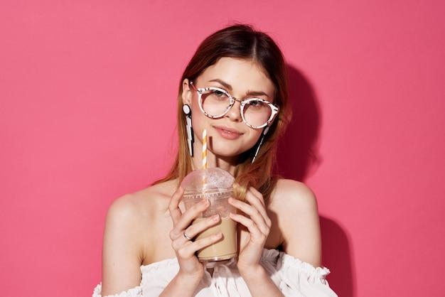 Ładna kobieta modne okulary ozdoba atrakcyjny wygląd luksusowy napój różowe tło. wysokiej jakości zdjęcie