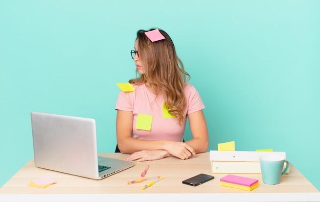 Ładna kobieta myśląca, wyobrażająca sobie lub marząca o widoku profilu. koncepcja telepracy