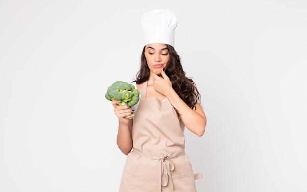 Ładna kobieta myśli, czuje się zwątpienie i zdezorientowana, nosząc fartuch i trzymając brokuły