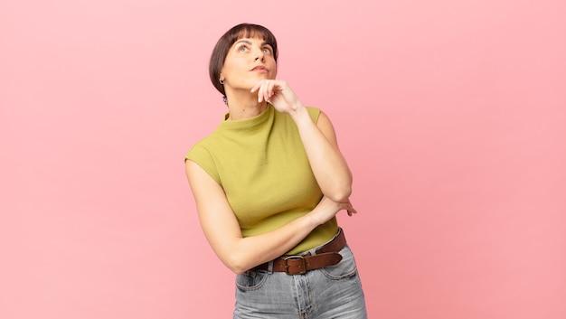 Ładna kobieta myśli, czuje wątpliwości i jest zdezorientowana, z różnymi opcjami, zastanawiając się, którą decyzję podjąć